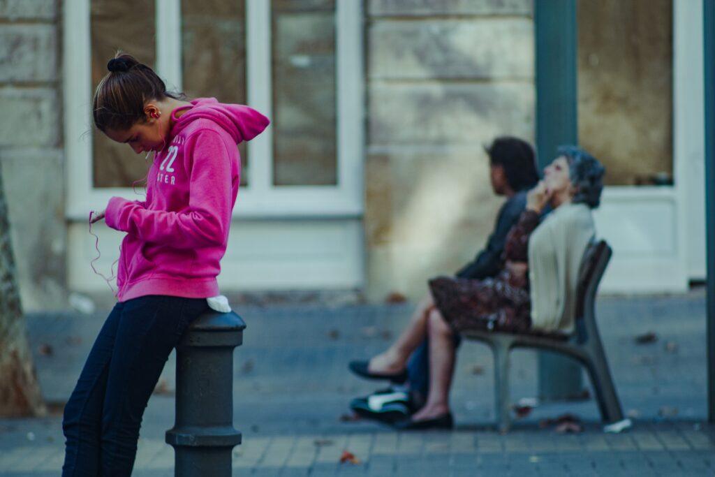 En la fotografía, aparecen tres personas en una plaza. Al fondo de la imagen, en un banco, están sentadas dos de ellas. Una persona que está mirando una pared y a su lado una persona mayor mayor que mira pensativa al cielo mientras se toca la barbilla. Tiene las piernas cruzadas. En otro lado de la plaza, una persona menor de edad con sudadera rosa consulta su móvil con los cascos puestos. Está apoyada en un palo de hierro que forma parte del inmobiliario urbano.
