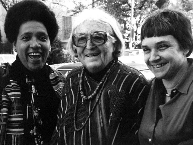 Retrato de tres mujers juntas que sonríen confidentes. Parecen amigas. De izquierda a derecha son Audre Lorde, Meridel Lesueur y Adrienne Rich. La foto es de 1980.